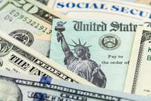Macro View Of The Statue Of Liberty On A United States Treasury Check With Social Security Card In Background.