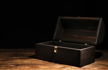 Empty Treasure Chest On Wooden Table Against Black Background. Space For Text