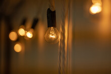 Round Small Bulb Glowing With Warm Orange Light Hang On A White Wall. Loft-style Decor. The Bulbs Are Connected To Each Other Like A Garland. Close-up, Bokeh Blurred Background