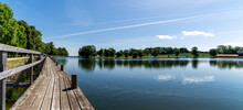 Idyllic Lake With A Wooden Boardwalk Along The Side And Sailboats Moored In The Background