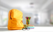 Yellow Backpack On Table Empty Copy Space. School Supplies. Education Objects.