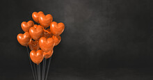 Orange Heart Shape Balloons Bunch On A Black Wall Background. Horizontal Banner.