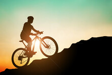 Mountain Bike Silhouette Training In The High Mountains In The Evening, Beautiful Colors. Silhouette Of A Mountain Biker Riding His Bike Up A Mountain. Travel And Adventure Concept