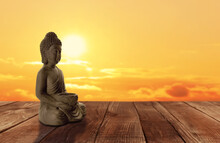 Beautiful Stone Buddha Sculpture On Wooden Surface At Sunset. Space For Text