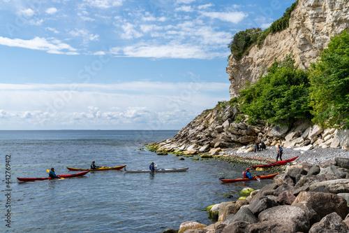 Obraz na plátně group of sea kayakers make a landing on a rocky beach on the coast of Denmark at