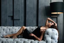 Beautiful Woman In Elegant Dress On Sofa Indoors. Luxury Lifestyle