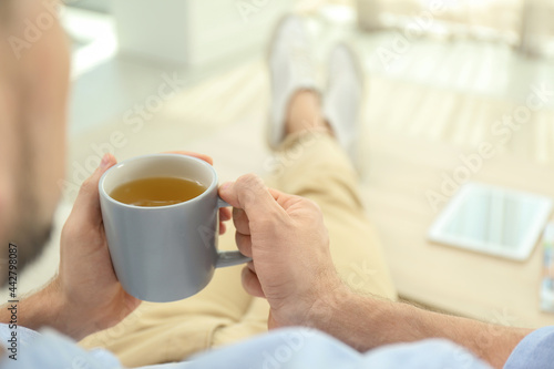 Obraz na plátně Man with cup of hot tea relaxing at home, closeup. Space for text