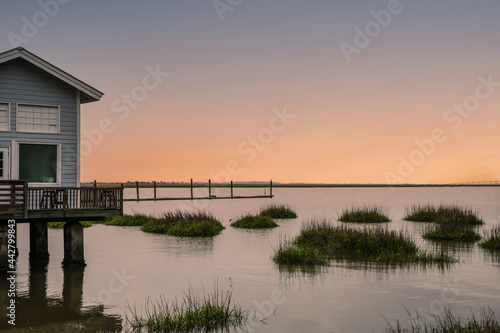 Fotografie, Obraz Sunsetting on the marshes by a house with a pier with tufts of grasses