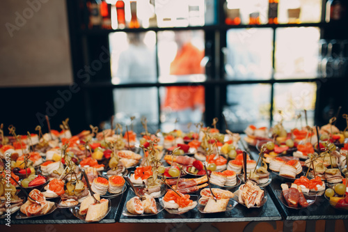 Fényképezés Food catering appetizers snacks on a tray on table.