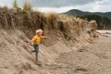 Blonde Haired Child Running Down Sand Dune In New Zealand