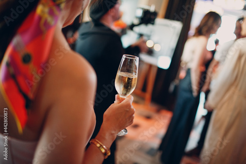 Stampa su Tela rear view woman holding misted chilled glass of champagne in hand at party