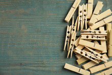 Pile Of Clothes Pins On Blue Wooden Table, Flat Lay. Space For Text