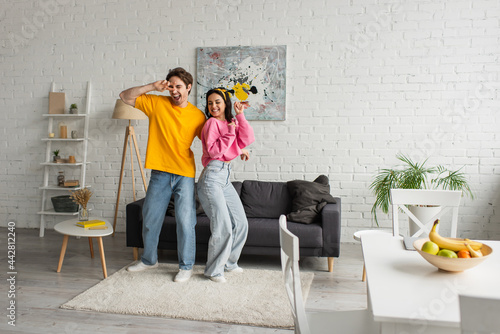 smiling young couple in casual clothes dancing in modern loft