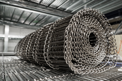 Fototapeta Metal stainless steel wire conveyor coiled and lying in a rack.