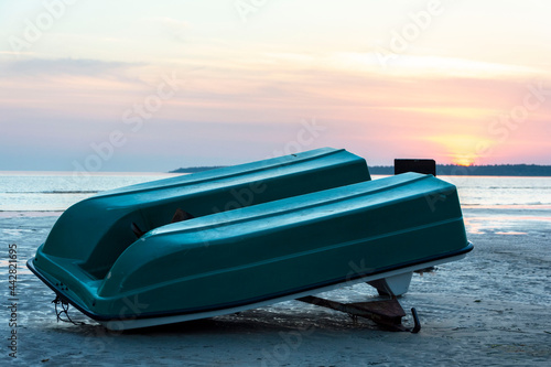 Fotografie, Obraz an old plastic inverted boat on the shore of the sea bay, an old catamaran, a pr