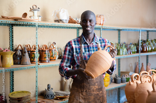 Foto Smiling afro craftsman offering for sale different stoneware and ceramic product