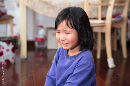 Photo Aggrieved four-year-old girl sitting on the floor and crying