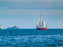 Classic Style Yacht With Red Hull Sails Past Green Buoy On Beautiful Deep Blue Sea.