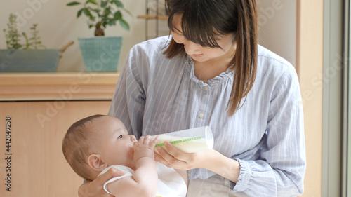 Photo ハーフの赤ちゃんにミルクを上げるお母さん
