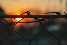 A Grating With Barbed Wire In The Evening At Sunset As A Symbol Of Imprisonment, Unfreedom