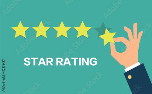 Fotografia Hand pressing five gold stars on green background