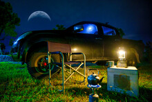 Light From Antique Oil Lamps, Kettle On Portable Gas Stoves, Portable Tables And Chairs, Night View With Pickup Trucks In The Forest.