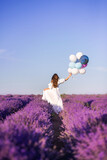 girl in a long white dress walks in a field of lavender. View from the back. In the hands of a large bunch of balloons