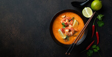Tom Yum Kung Spicy Thai Soup With Shrimp In A Black Bowl On A Dark Background, Top View