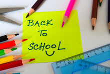 Back To School Message On Yellow Sticky Note With Stationery Scattered Around Isolated On White Background