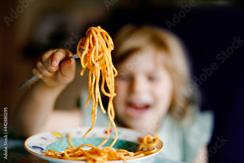 Fotografía Adorable toddler girl eat pasta spaghetti with tomato bolognese with minced meat