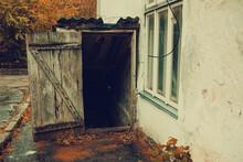 Old Cellar Entrance With Wooden Door On A Rainy Day Near An Asylum, Horror Concept
