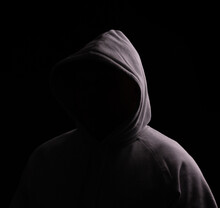 Hooded Person With No Face Showing, Just A Dark Area In That Place, Ideal For Logo's And Copy. Black Background With Moody Lighting.