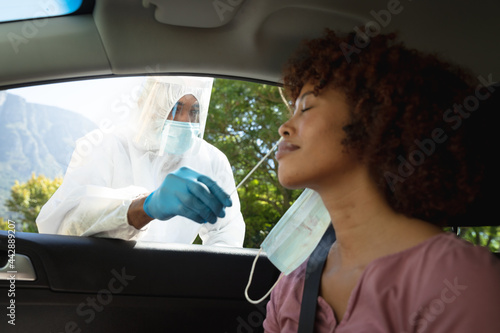 Medical worker wearing ppe suit taking swab test of african american woman sitting in car