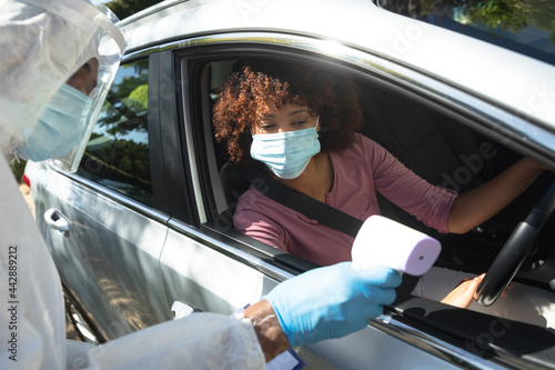 Medical worker wearing ppe suit taking temperature of african american woman sitting in car