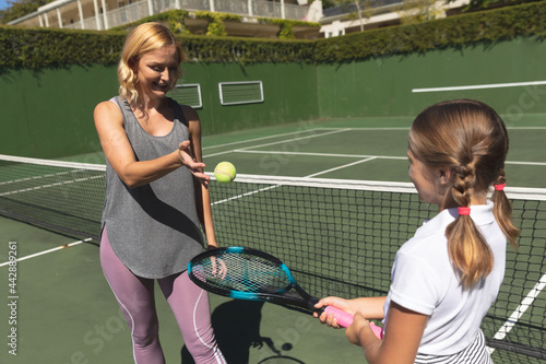 Happy caucasian mother with daughter outdoors, playing tennis on tennis court