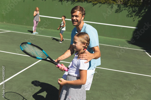 Happy caucasian couple with daughter and son outdoors, playing tennis on tennis court