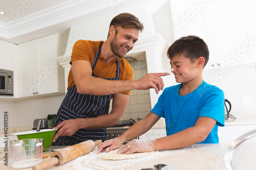 Caucasian father and son baking and smiling in kitchen