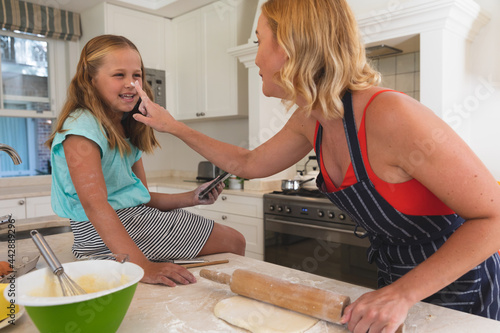 Happy caucasian mother and daughter having fun baking in kitchen