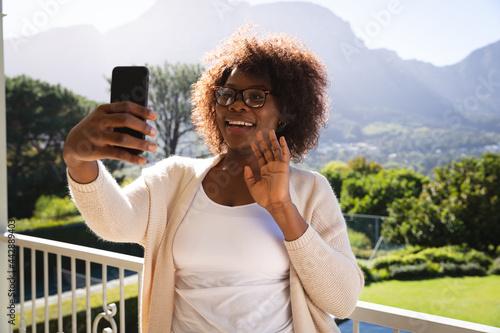 Happy african american woman on sunny balcony of country home making video call on smartphone