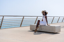 Attractive Elegant Black Woman Resting On Bench On Sunny Promenade