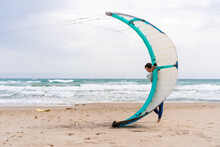 Sportswoman With Power Kite On Shore Against Stormy Sea