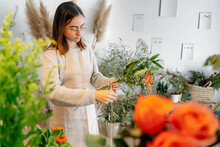 Young Ethnic Female Employer Composing Gentle Flowers Bouquet In Florist Store