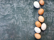 White And Brown Eggs Of Domestic Chickens Border Or Line On Old Wooden Gray Painted Texture Background. Closeup, Copy Space, Mockup, Top View.