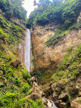 Young Adventurous Guy Standing In Front Of A Huge Wild Waterfall In Azores Islands.