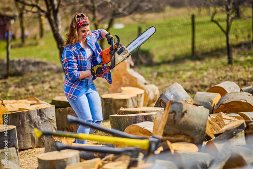 Fotografiet Young Woman using chainsaw to cut a log for firewood.