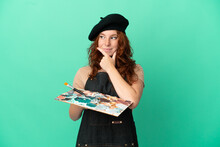 Teenager Redhead Artist Holding A Palette Isolated On Green Background Having Doubts