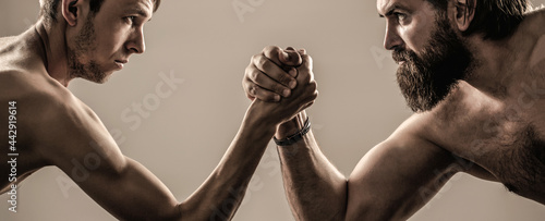 Photo Two man's hands clasped arm wrestling, strong and weak, unequal match