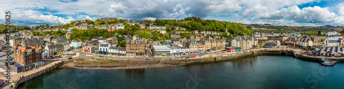 Fotografie, Obraz A panorama aerial view across the seafront in the town of Oban, Scotland on a su