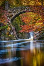 Old Stone Bridge Over The Black Linn Falls In Perthshire Scotland In Full Autumn Colours
