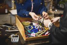 Butiksägare Visar Smycken För Kund I Butik